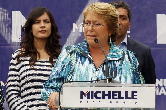 FILE - In this Nov. 19, 2013, file Photo, Chile's presidential candidate Michelle Bachelet speaks at a campaign rally in Santiago, Chile. Pictured left is newly elected member of Congress and former student leader Camila Vallejo of the Communist Party. Vallejo is now a member of Congress and a Bachelet ally, but the key university student unions are led by anarchists who are vowing to make life impossible for Bachelet if she doesn't follow through. (AP Photo/Luis Hidalgo,File)