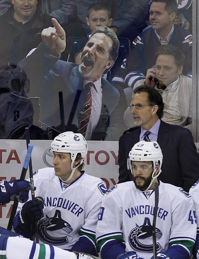 Winnipeg Jets fans taunt Vancouver Canucks coach John Tortorella during the first period of an NHL hockey game Wednesday, March 12, 2014, in Winnipeg, Manitoba. (AP Photo/The Canadian Press, John Woods)