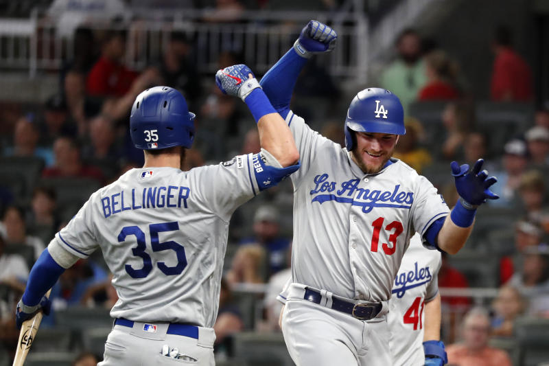 Los Angeles Dodgers' Max Muncy (13) celebrates with Cody Bellinger (35) after hitting a three-run home in the seventh inning of a baseball game against the Atlanta Braves, Friday, Aug. 16, 2019, in Atlanta. (AP Photo/John Bazemore)