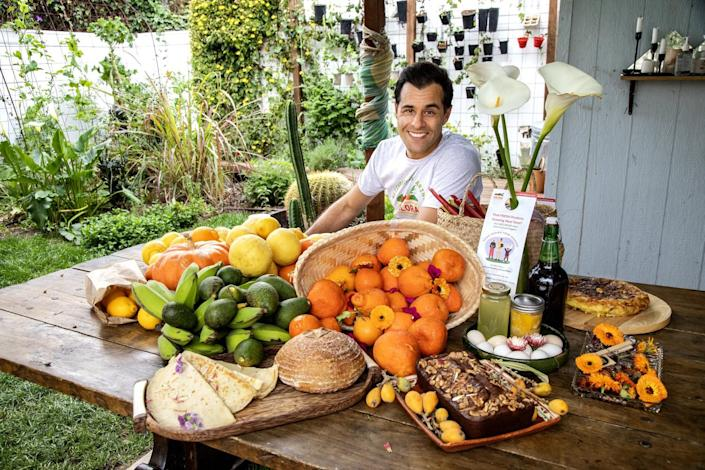 Ryan Xavier sits at a table laden with bread, fruit and other edible items.