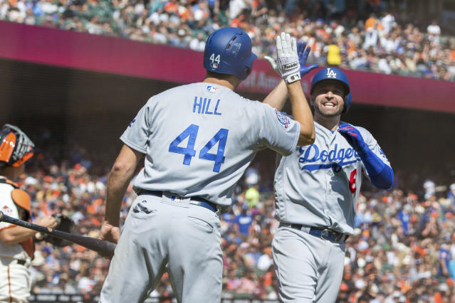 Los Angeles Dodgers Brian Dozier, right, celebrates with Rich Hill (44) after he hit a two-run home run against the San Francisco Giants in the third inning of a baseball game in San Francisco, Sunday, Sept. 30, 2018. (AP Photo/John Hefti)