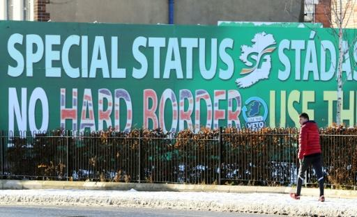 A pedestrian walks past a billboard in west Belfast on December 8, 2017 erected by Republican Party Sinn Fein calling for a special status for Northern Ireland with respect to Brexit and no hard borders in Ireland