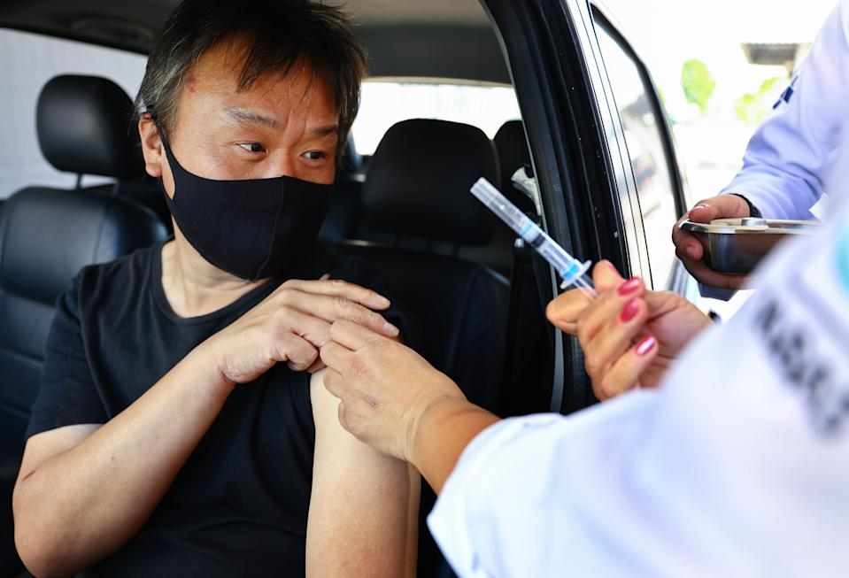 SAO PAULO, BRAZIL - MAY 21: A driver reacts after receiving a dose of the AstraZeneca COVID-19 vaccine from a public health worker at a drive-through vaccination post on May 21, 2021 in Sao Paulo, Brazil. Around 20 percent of Brazilians have received their first vaccination dose. Health experts are warning that Brazil should brace for a new surge of COVID-19 amid a slow vaccine rollout and relaxed restrictions. The state of Sao Paulo has registered over 3 million cases of COVID-19 and more than 100,000 deaths. Over 440,000 people have been killed in Brazil by COVID-19, second only to the U.S. (Photo by Mario Tama/Getty Images)