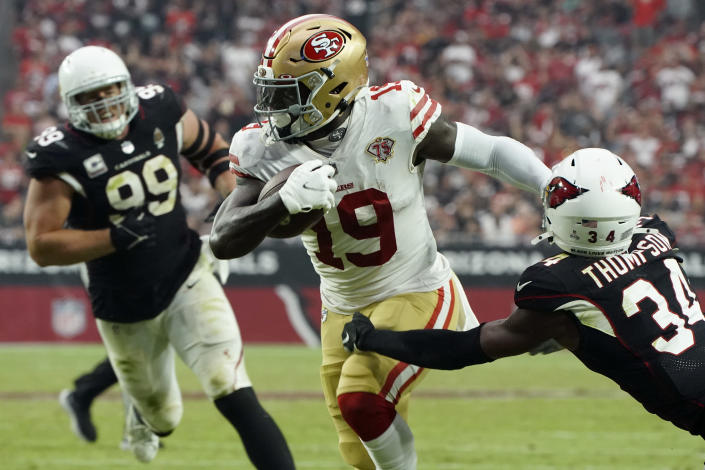 San Francisco 49ers wide receiver Deebo Samuel (19) breaks the tackle of Arizona Cardinals free safety Jalen Thompson (34) for a touchdown during the second half of an NFL football game, Sunday, Oct. 10, 2021, in Glendale, Ariz. (AP Photo/Darryl Webb)