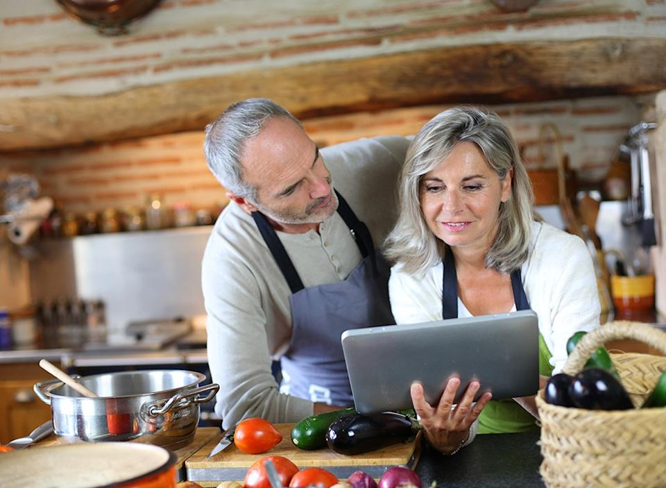older couple cooking with tablet