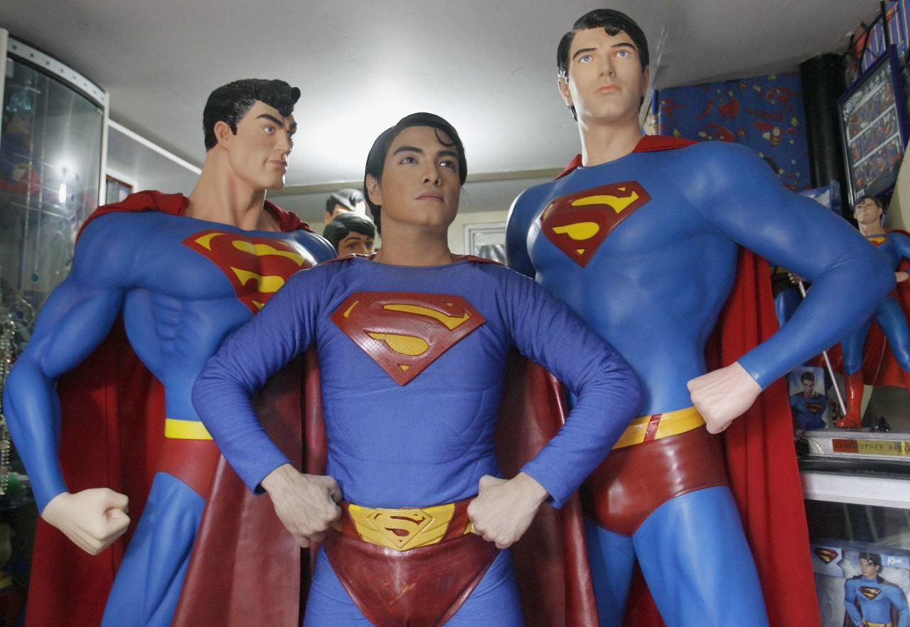 "Herbert Chavez poses with his life-sized Superman statues inside his house in Calamba Laguna, south of Manila October 12, 2011. In his idolization of the superhero, Chavez, a self-professed ""pageant trainer"" who owns two costume stores, has undergone a series of cosmetic surgeries for his nose, cheeks, lips and chin down to his thighs and even his skin color to look more like the ""Man of Steel"". The final result bears little resemblance to his old self. REUTERS/Cheryl Ravelo (PHILIPPINES - Tags: SOCIETY TPX IMAGES OF THE DAY)"