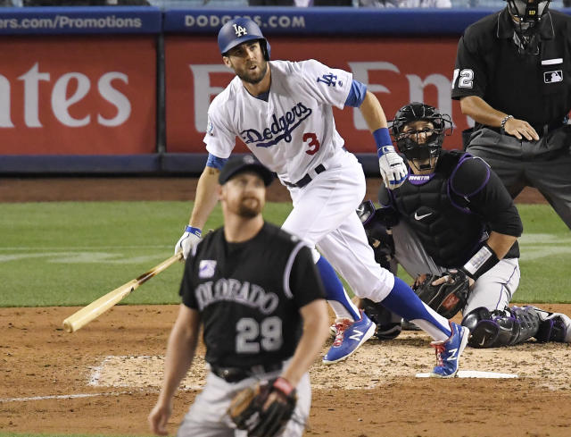 Los Angeles Dodgers' Chris Taylor, center, runs to first on a two-run home run off Colorado Rockies relief pitcher Bryan Shaw, front, during the sixth inning of a baseball game Tuesday, May 22, 2018, in Los Angeles. (AP Photo/Mark J. Terrill)