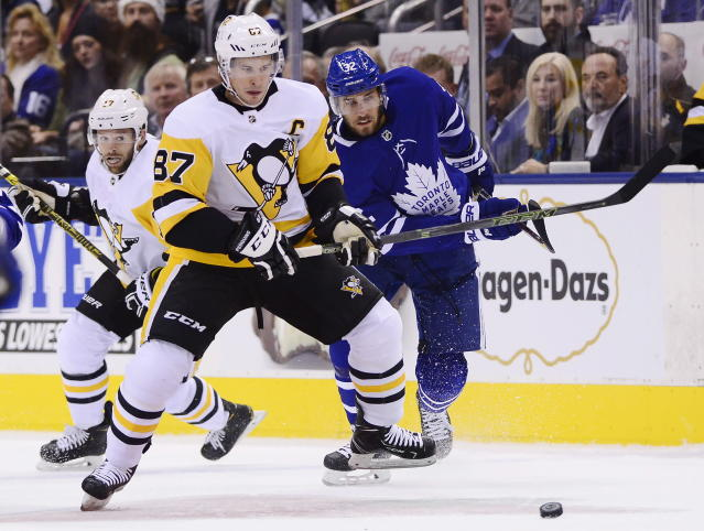 Pittsburgh Penguins centre Sidney Crosby (87) and Toronto Maple Leafs left wing Josh Leivo (32) battle for the puck during first period NHL hockey action in Toronto on Thursday, Oct. 18, 2018. (Frank Gunn/The Canadian Press via AP)