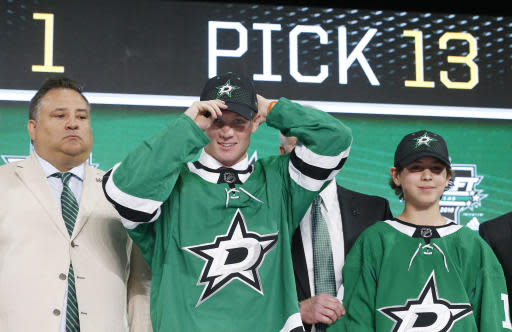 Ty Dellandrea, second from left, puts on a cap after being selected by the Dallas Stars during the NHL hockey draft in Dallas, Friday, June 22, 2018. (AP Photo/Michael Ainsworth)