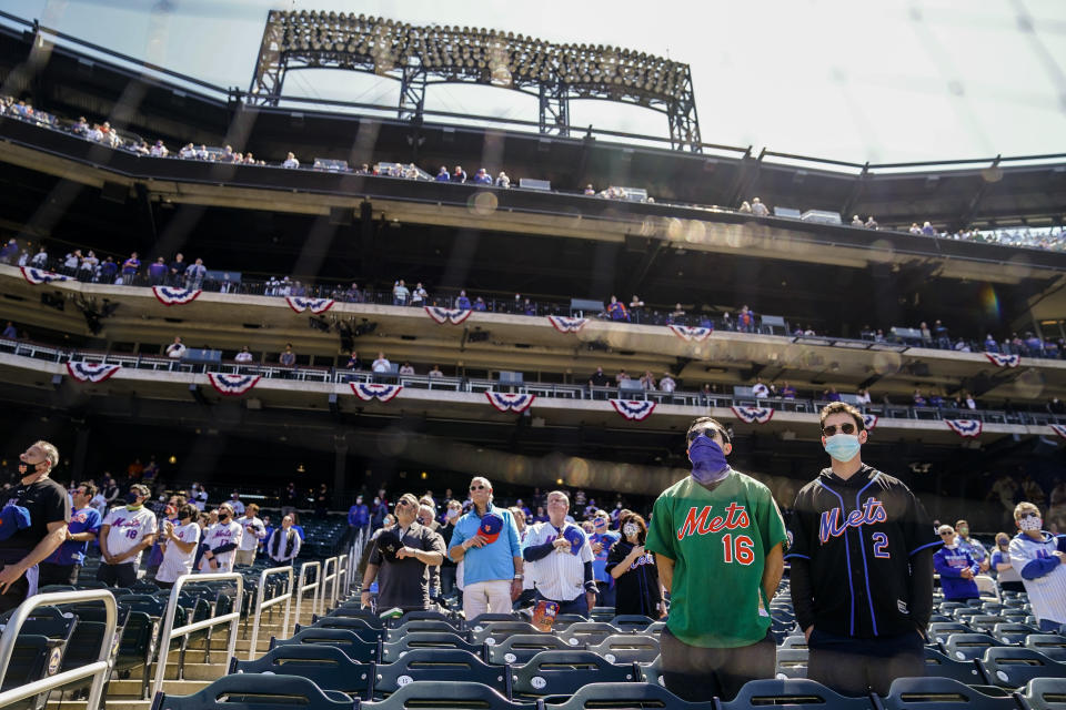 Fans stand for pre-game ceremonies before a baseball game between the New York Mets and the Miami Marlins, Thursday, April 8, 2021, in New York. (AP Photo/John Minchillo)