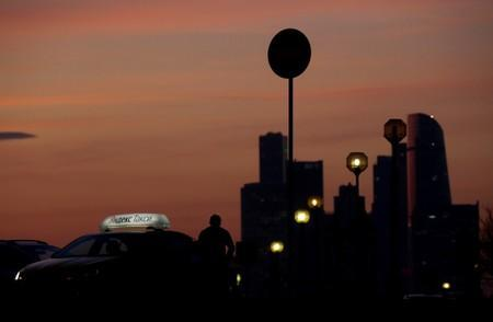 FILE PHOTO: A driver rests next to a car with Yandex Taxi logo on the roof during sunset in Moscow