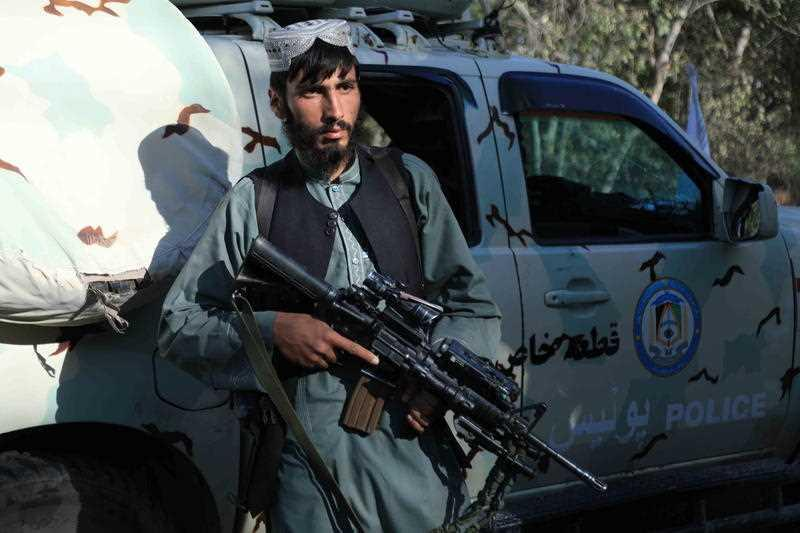 Taliban use a captured Afghan security forces vehicle as they stand guard at a checkpoint as they took control of Herat, Afghanistan.