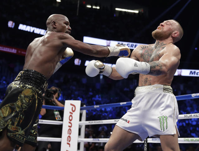 Floyd Mayweather Jr. hits Conor McGregor in a super welterweight boxing match Saturday, Aug. 26, 2017, in Las Vegas. (AP)