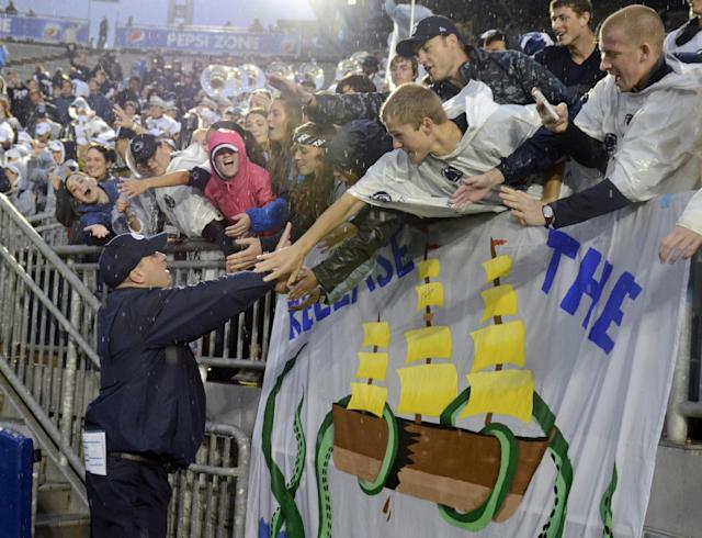 Penn State head coach Bill O' Brien, left, thanks fans in the student section of Beaver Stadium after defeating Kent State 34-0 in an NCAA college football game in State College, Pa., Saturday, Sept. 21, 2013. (AP Photo/John Beale)
