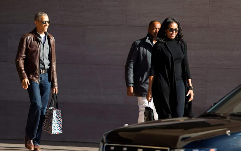Barack and Michelle Obama smile for the cameras as they leave the National Gallery of Art in Washington on Sunday - AP