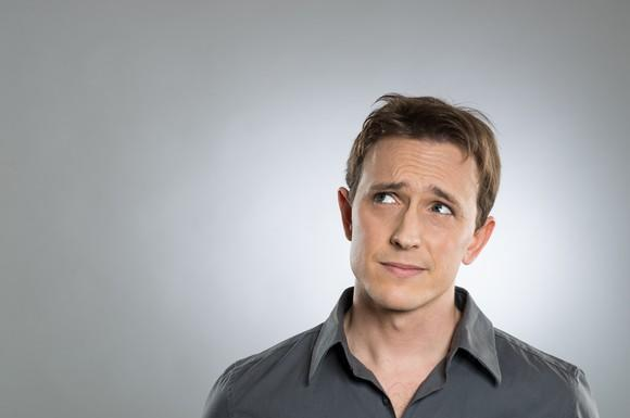 Man looking puzzled against a gray background