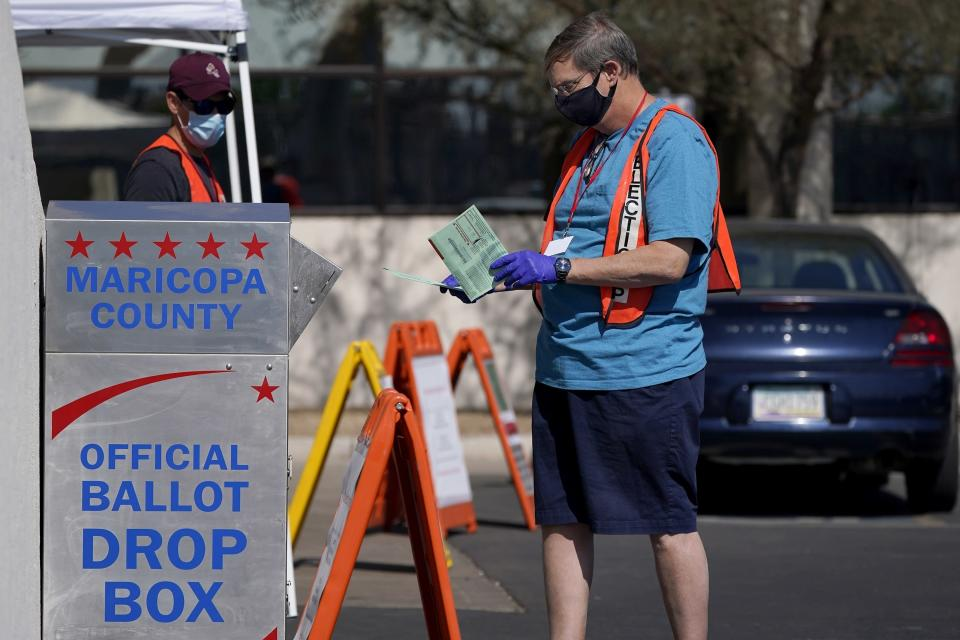 FILE - In this Tuesday, Oct. 20, 2020 file photo, volunteers help voters as voters drop off their ballots at the Maricopa County Recorder's Office in Phoenix. An Associated Press investigation has found county election officials throughout Arizona have identified fewer than 200 cases of potential voter fraud from last year's presidential election that require review by local prosecutors. The findings undermine claims by former President Donald Trump and his allies that widespread fraud is to blame for his loss in Arizona. (AP Photo/Ross D. Franklin, File)