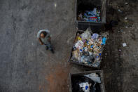 A homeless man walks next to trash dumpsters in Beirut, Lebanon, Sunday, July 12, 2020. Lebanon should quickly form a reform-minded government to carry out badly needed reforms to help get the tiny country out of its severe economic crisis where the Real GDP growth is projected to contract nearly 20% in 2020 and a crash in local currency led to triple-digit inflation rates, the World Bank said Tuesday. (AP Photo/Hassan Ammar)