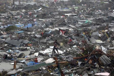 A man stands atop debris as residents salvage belongings from the ruins of their houses after Typhoon Haiyan battered Tacloban city in central Philippines November 10, 2013. REUTERS/Erik De Castro