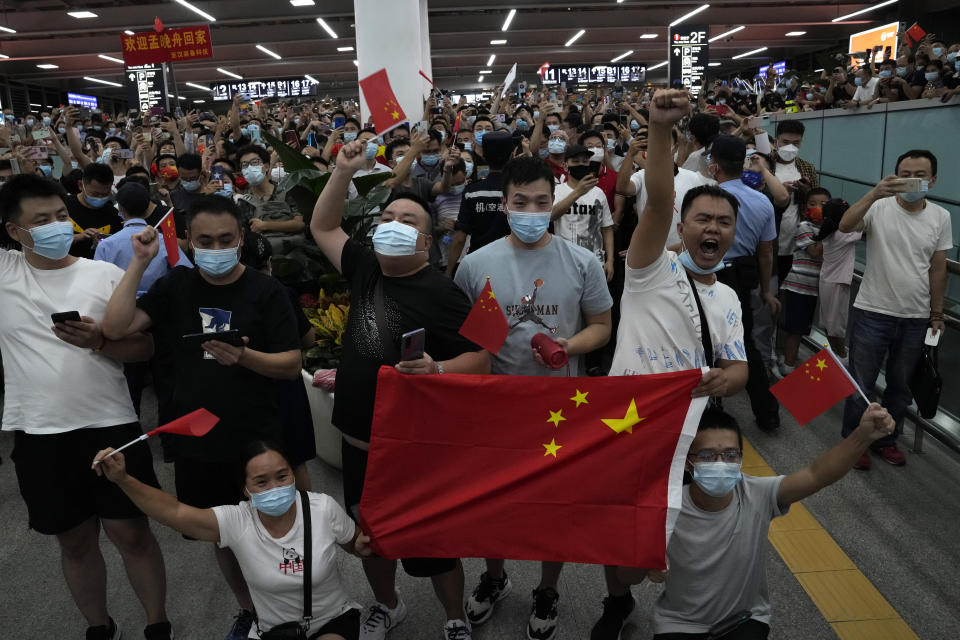 Residents holdings flags and chanting cheer as they wait for the arrival back to China of Meng Wanzhou, an executive of Chinese tech giant Huawei who was held by Canada for more than two years at America's request, at the airport in Shenzhen in southern China's Guangdong Province, on Sept. 25, 2021. Nine months into U.S. President Joe Biden's administration, there are signs of movement in what has been a fraught U.S.-China relationship. (AP Photo/Ng Han Guan)