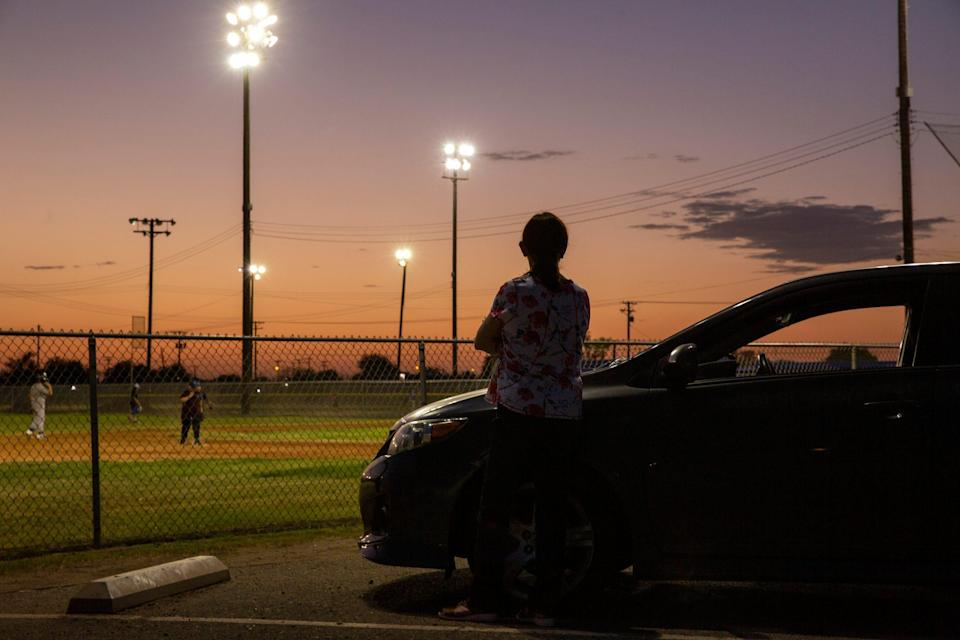 A woman watches youth play baseball near Kennedy Middle School in El Centro, Calif., on July 7, 2021. The City of El Centro consistently ranks as having the highest unemployment rate in the country.