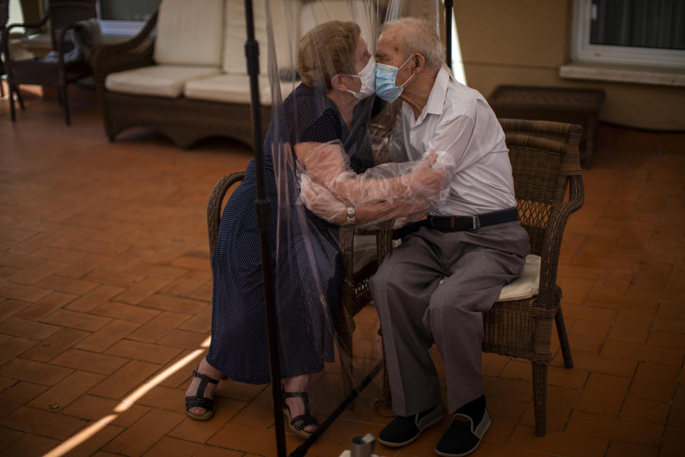 FILE - In this Monday, June 22, 2020 file photo, Agustina Canamero, 81, and Pascual Perez, 84, hug and kiss through a plastic film screen to avoid contracting the new coronavirus at a nursing home in Barcelona, Spain. Nations are struggling to reconcile cold medical advice with a holiday tradition that calls for big gatherings in often poorly ventilated rooms, where people chat, shout and sing together, providing an ideal conduit for a virus that has killed over 350,000 people in Europe so far. (AP Photo/Emilio Morenatti, File)