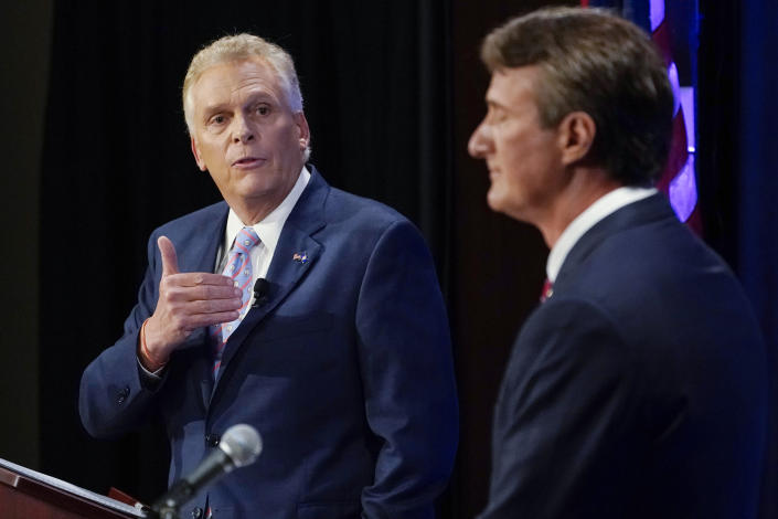 FILE - In this Sept. 16, 2021, file photo Democratic gubernatorial candidate former Governor Terry McAuliffe, left, gestures as Republican challenger, Glenn Youngkin, listens during a debate at the Appalachian School of Law in Grundy, Va. McAuliffe has generally led in public polling, but recent surveys have suggested his lead is tightening. His race against Glenn Youngkin is one of the country's most competitive and closely watched political matchups of the year. (AP Photo/Steve Helber, File)