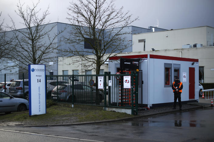 A security guard stands at the entrance of the Novasep factory in Seneffe, Belgium, Friday, Jan. 29, 2021. Amid a dispute over expected shortfalls, the European Union is looking at legal ways to guarantee the delivery of all the COVID-19 vaccine doses it bought from AstraZeneca and other drugmakers as regulators are set to consider approving the Anglo-Swedish company's vaccine for use in the 27-nation EU. (AP Photo/Francisco Seco)