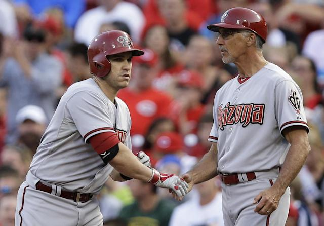 Arizona Diamondbacks' Miguel Montero, left, is congratulated by first base coach Dave McKay after Montero got a hit off Cincinnati Reds starting pitcher Homer Bailey to drive in a run in the fourth inning of a baseball game, Monday, July 28, 2014, in Cincinnati. (AP Photo/Al Behrman)