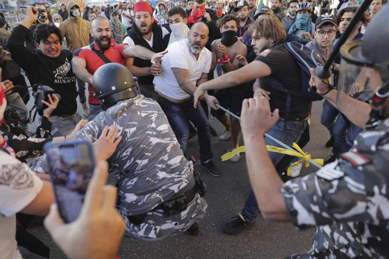 Anti-government protesters clash with riot police on a road leading to the parliament building in downtown Beirut, Lebanon, Tuesday, Nov. 19, 2019. Scuffles have broken out in central Beirut as hundreds of anti-government protesters tried to prevent lawmakers from reaching Parliament. (AP Photo/Hassan Ammar)