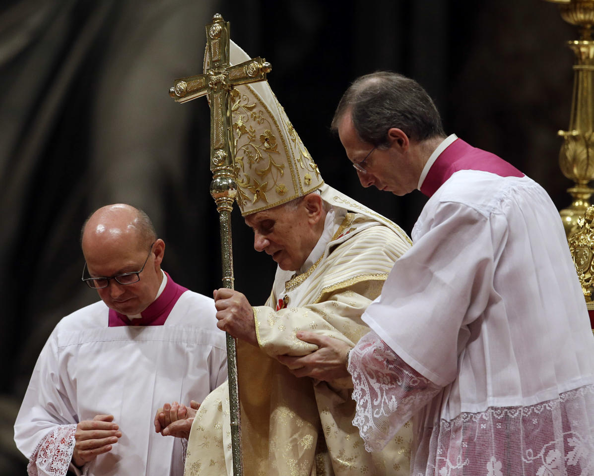 Pope Benedict XVI is helped on to the altar by Bishop Guido Marini, right, during the Christmas Eve Mass in St. Peter's Basilica at the Vatican, Monday, Dec. 24, 2012. (AP Photo/Gregorio Borgia)