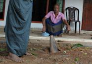 A mortar shell is seen lodged in front of a house at Salawa on the edge of the Sri Lankan capital Colombo on June 6, 2016, hours after explosion at an ammunition depot at the neighbouring military complex
