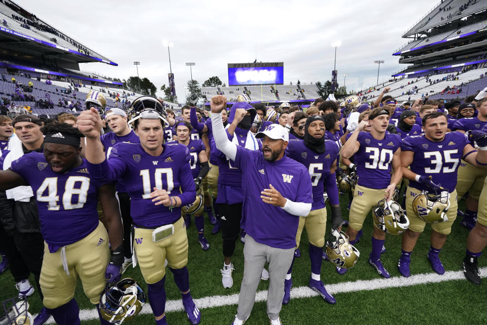 Washington head coach Jimmy Lake, center, leads the team in singing the school fight song to fans after the team beat Arkansas State in an NCAA college football game Saturday, Sept. 18, 2021, in Seattle. Washington won 52-3. (AP Photo/Elaine Thompson)