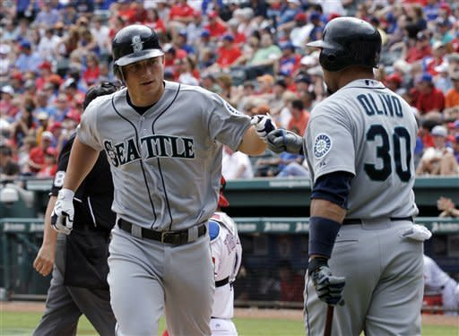Seattle Mariners' Kyle Seager is congratulated by Miguel Olivo (30) on his solo home run off Texas Rangers' Derek Holland in the seventh inning of a baseball game Thursday, April 12, 2012, in Arlington, Texas. The Rangers won 5-3. (AP Photo/Tony Gutierrez)