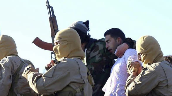 FILE - This Wednesday, Dec. 24, 2014, this image posted by the Raqqa Media Center, which monitors events in territory controlled by Islamic State militants with the permission of the extremist group, shows militants with a captured pilot, center right, wearing a white shirt in Raqqa, Syria. (AP Photo/Raqqa Media Center, File)