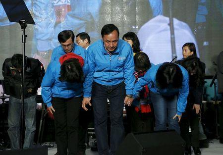 Taiwan's ruling Nationalist Kuomintang Party (KMT) presidential candidate Eric Chu (C) and his wife Kao Wan-ching (R) bow as Chu concedes defeat in the elections in Taipei, Taiwan January 16, 2016. REUTERS/Olivia Harris