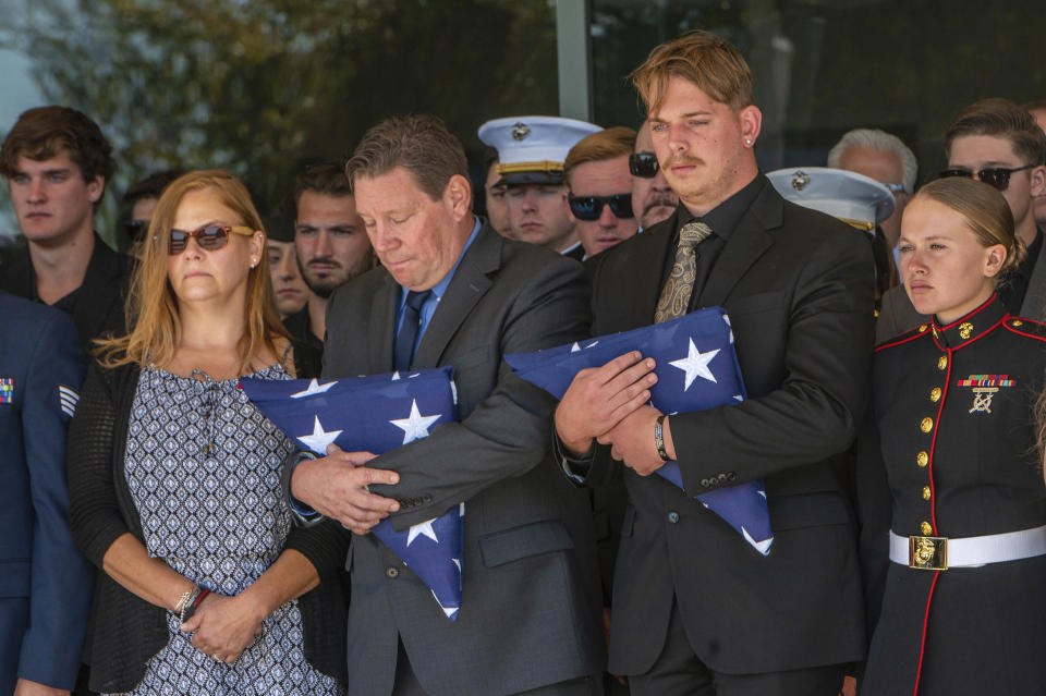 After the service for fallen Marine Sgt. Nicole Gee, her father Richard Herrera, center, and husband Jarod Gee, right, hold U.S. flags as her casket is moved to the hearse at Bayside Church Adventure Campus in Roseville, Calif., Saturday Sept. 18, 2021. Sgt. Gee lost her life, along with 12 other U.S. service members, in the bombing attack at the Kabul airport in Afghanistan on Aug. 26. (Renee C. Byer/The Sacramento Bee via AP)