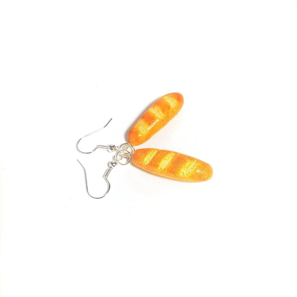 """<h2>Funky Earrings</h2><br>Nothing screams """"I'm queer"""" like funky earrings. The lesbian community on <a href=""""https://www.youtube.com/watch?v=GFicvaNzF7M"""" rel=""""nofollow noopener"""" target=""""_blank"""" data-ylk=""""slk:Tik Tok"""" class=""""link rapid-noclick-resp"""">Tik Tok</a> took this idea and ran with it. There's no specific brand or style for the earrings. They just have to be fun, quirky, and unique (major probs if it's hilariously weird!). <br><br><em>Shop <strong><a href=""""https://www.etsy.com/shop/qminishop"""" rel=""""nofollow noopener"""" target=""""_blank"""" data-ylk=""""slk:Qminishop"""" class=""""link rapid-noclick-resp"""">Qminishop</a></strong></em><br><br><strong>qminishop</strong> Miniature French Baguette Dangle Earring, $, available at <a href=""""https://go.skimresources.com/?id=30283X879131&url=https%3A%2F%2Fwww.etsy.com%2Flisting%2F928156221%2Fminiature-french-baguette-dangle-earring"""" rel=""""nofollow noopener"""" target=""""_blank"""" data-ylk=""""slk:Etsy"""" class=""""link rapid-noclick-resp"""">Etsy</a>"""