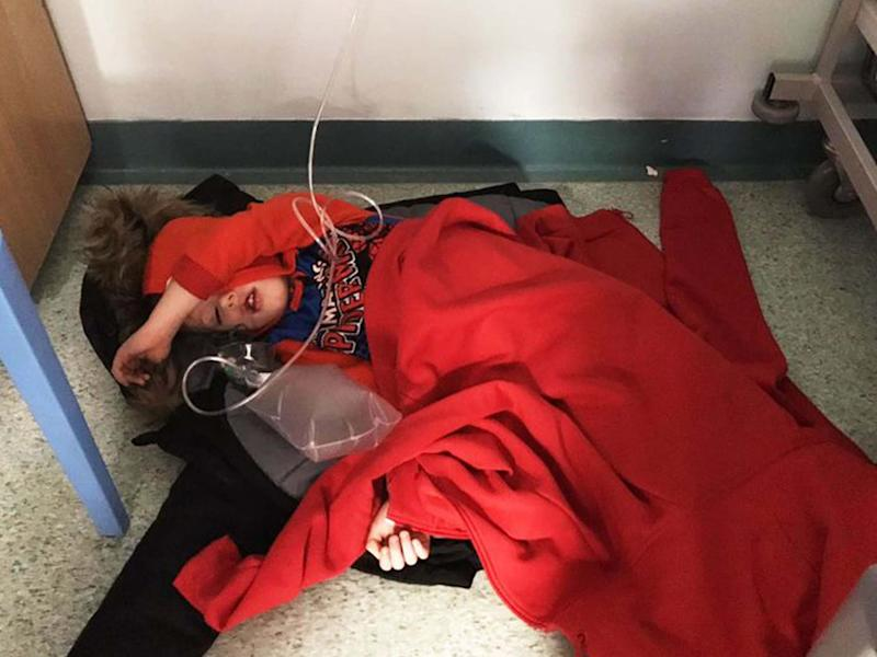 Four-year-old Jack Williment is covered in coats on the floor at Leeds General Infirmary due to a lack of beds: Mirror