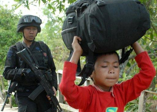 Police guard a Shiite boy as he is escorted to safety after the attacks in Sampang