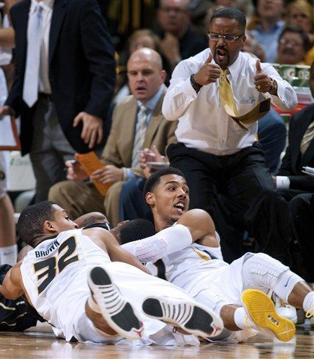Missouri's Phil Pressey, right, and Jabari Brown, scramble to get a ball on the floor in front of head coach Frank Haith during the first half of an NCAA college basketball game against Vanderbilt on Saturday, Jan. 26, 2013, in Columbia, Mo. Missouri won the game 81-59. (AP Photo/L.G. Patterson)