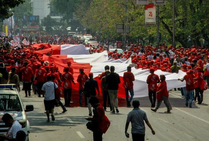 Outside parliament, red-and-white Indonesian flags dotted parts of the city but celebrations were muted under heavy security (AFP Photo/DANY KRISNADHI)
