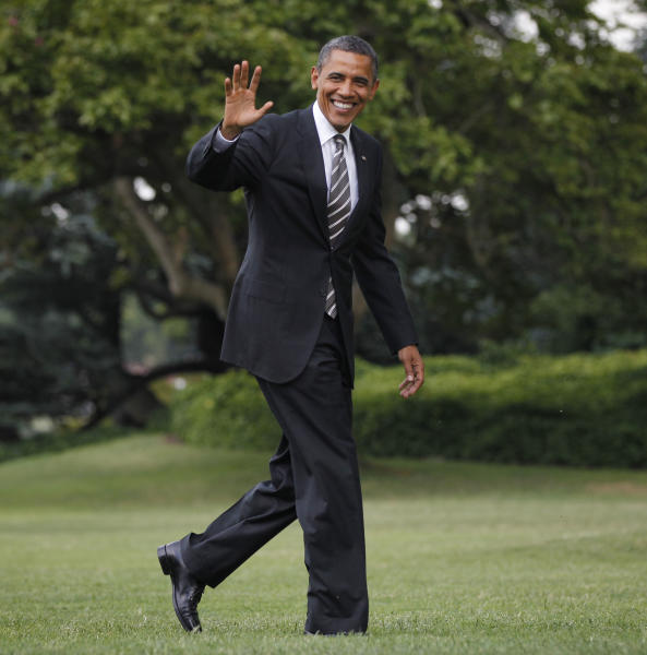 President Barack Obama waves as he walks across the South Lawn of the White House in Washington, following his arrival on Marine One helicopter, Tuesday, July, 10, 2012. (AP Photo/Pablo Martinez Monsivais)