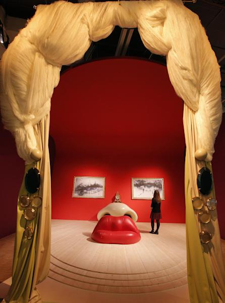 """In this photo taken Monday, Nov. 19, 2012, a visitor stands in the 'Mae West, 1934' room by Spanish artist Salvador Dali (1904-1989) during the presentation to the press of the exhibition """"Dali"""" at the Centre Pompidou modern art museum, in Paris. A major retrospective of Salvador Dali in Paris aims to rewrite the art history books, reconciling for the first time the last decades of his life _ when he was accused of money-making self-publicity through numerous television appearances _ with his earlier, respected Surrealist period. (AP Photo/Francois Mori)"""