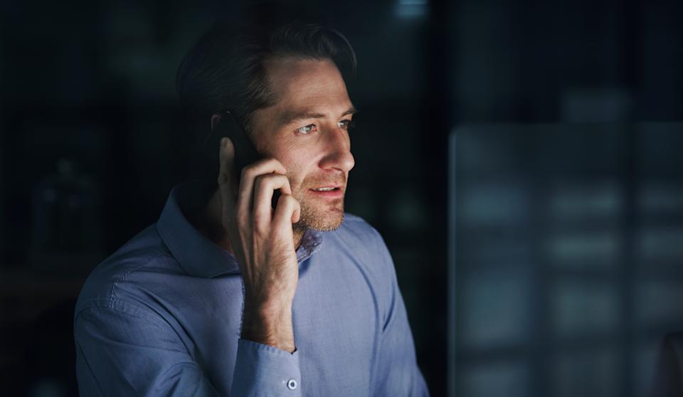 Shot of a mature businessman talking on a cellphone while working on a computer in an office at night