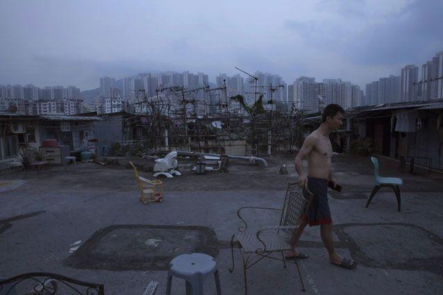 A resident walks outside his illegal rooftop hut. Photo: AP