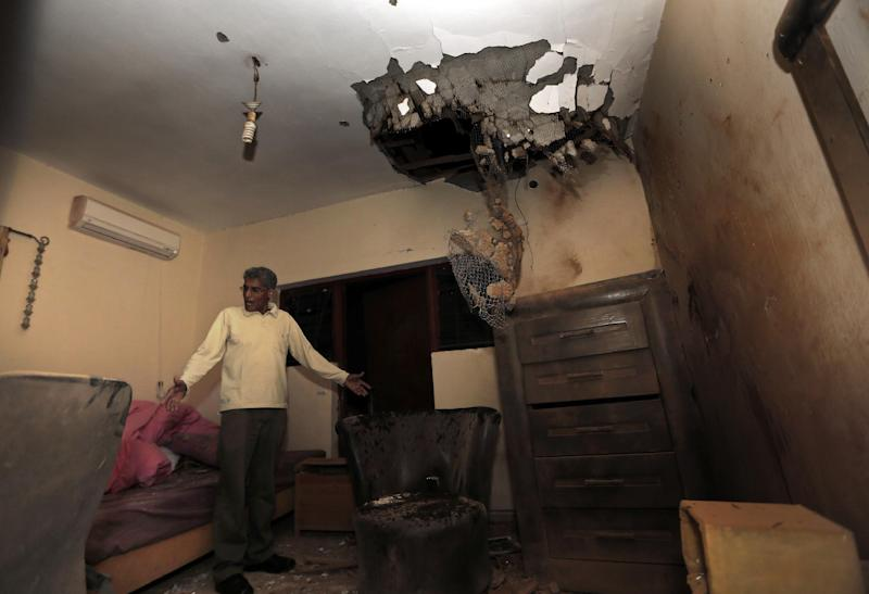 An unidentified Israeli man inspects the damage to a house caused by a rocket thought to have been fired by Palestinian militants from the Gaza Strip in the southern Israeli town of Sderot, Sunday, Nov. 11, 2012. Hostilities along the Gaza-Israel border escalated sharply over the weekend, with bombardments from Gaza causing rare Israeli casualties and Israeli strikes killing several Palestinians. (AP Photo/Tsafrir Abayov)