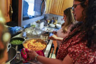 HOLD FOR ENRIC MARTI Vivian Zayas cooks rice and beans by her mother's recipe, the recently deceased Ana Martinez, as she and her sister Alexa prepare Thanksgiving dinner, Thursday, Nov. 26, 2020, in Deer Park, N.Y. (AP Photo/John Minchillo)