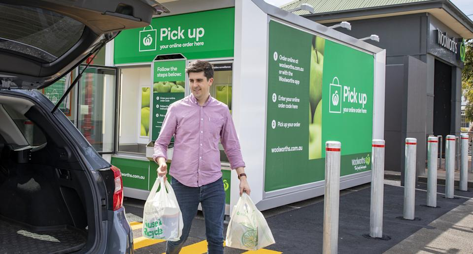 A man is taking groceries from a new Woolworths click and collect locker to the boot of his car.