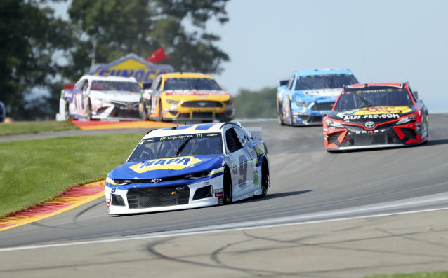 """Chase Elliott leads the field thought the area known as """"The Bus Stop"""" during a NASCAR Cup Series auto race at Watkins Glen International, Sunday, Aug. 4, 2019, in Watkins Glen, N.Y. (AP Photo/John Munson)"""